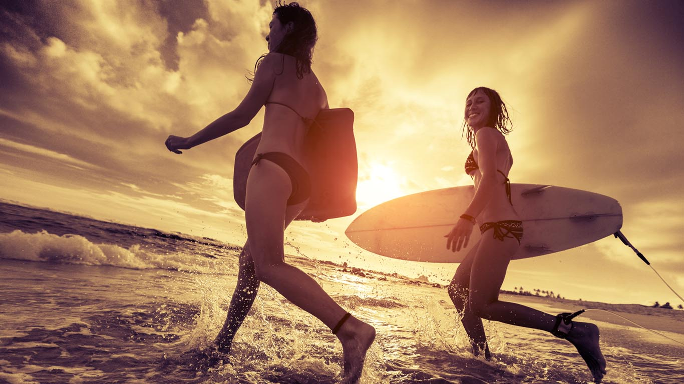 Two ladies surfers running with surfboards into the sea at sunset